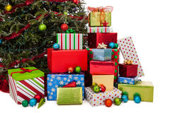 Stack of Christmas presents. In front of a tree isolated on a white background royalty free stock images