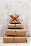 Stack of Christmas Presents. Plain brown paper wrapped gifts tied with twine and stacked in the shape of a Christmas tree with star, against rustic white wood royalty free stock photography