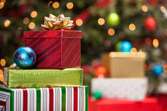Stack of Christmas presents. Stack of wrapped Christmas presents and ornaments under a Christmas tree with defocused lights Stock Image