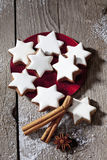 Stack of cinnamon stars on plate with cinnamon sticks ans star anise on wooden floor Royalty Free Stock Photography