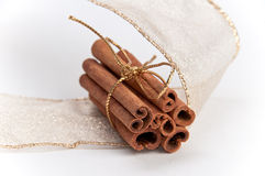 Stack of cinnamon sticks with gold ribbons. Stack of cinnamon sticks tied in gold ribbon and decorated with gold Christmas ribbon on white isolating background Stock Images