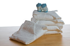 Stack of classical square white cloth diapers with blue socks. On white background - with clipping path Stock Images