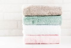 Stack clean bath towels. Spa relax and bath concept, stack clean bath towels colorful cotton terry textile in bathroom white background, copy space top view Stock Photo