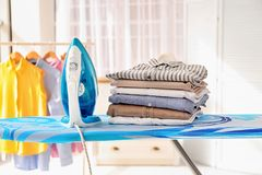 Stack of clean clothes and iron on board Stock Image
