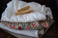 Stack of clean clothes and linen towels, clothespins on table stock image