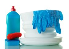 Stack of clean dishes, detergent, sponges and gloves isolated on white. Background Stock Photos