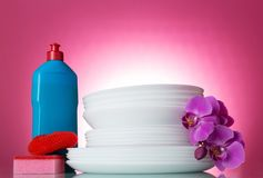 Stack of clean dishes, detergent and sponges, Orchid flower, isolated on red. Background Stock Photo