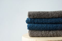 Stack of clean folded navy blue beige terry towels on wooden char gray wall background. Laundry spa wellness cleanliness concept stock photo