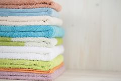 A stack of clean multi-colored towels on a wooden surface. stock photos