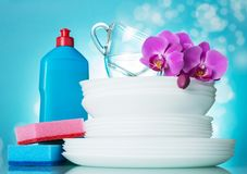 A stack of clean plates, glass cups, on top flower, near detergent and sponge on light blue. Background Royalty Free Stock Image
