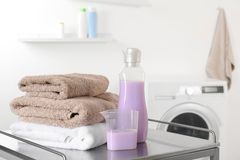 Stack of clean towels and detergent on table. In laundry room. space for text stock photo