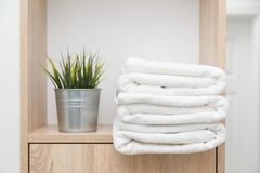 Stack of clean towels on shelf with greens in bucket. Stack of clean towels on shelf with greens in pot royalty free stock photos