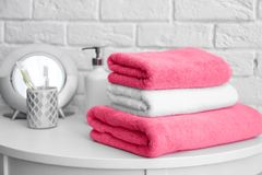Stack of clean towels and toiletries on table. Near white brick wall Stock Images