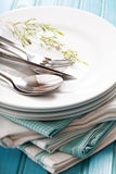 A stack of clean white plates with sliverware Stock Photo