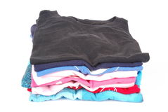 Pile of pressed clothes. A stack of a boys ironed t-shirts in various colors. Image isolated on white studio background Stock Images