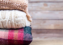 Stack of clothes from knitted knitwear on a wooden background Royalty Free Stock Photo