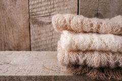 Stack of clothes from knitted knitwear on a wooden background, copy space. Autumn fall winter homely concept. Stack of clothes from knitted knitwear on a wooden stock photo