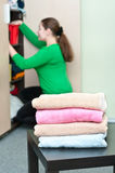 Stack of clothes and young woman working. Stack of clothes and young caucasian woman arranging things in the wardrobe on background Royalty Free Stock Photos