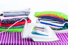 Stack of clothing and iron on a white background Stock Photo