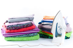Stack of clothing and iron on a white background Royalty Free Stock Photography