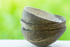 Stack of coconut shell bowls on green foliage background. Artisan craftsmanship eco-friendly materials dishware. Clean eating. Concept. Poster banner with copy stock photography