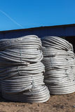 Stack of coiled plastic pvc Polyethylene Corrugated drainage pipes for sewer system outdoor warehouse Royalty Free Stock Image