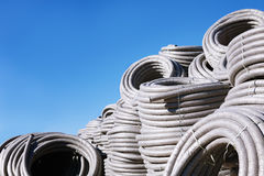 Stack of coiled plastic pvc Polyethylene Corrugated drainage pipes for sewer system outdoor warehouse Royalty Free Stock Images