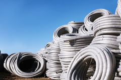 Stack of coiled plastic pvc Polyethylene Corrugated drainage pipes for sewer system outdoor warehouse Royalty Free Stock Photo