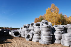 Stack of coiled plastic pvc Polyethylene Corrugated drainage pipes for sewer system outdoor warehouse Stock Photos