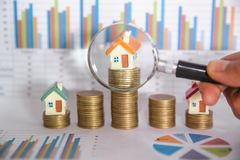 Stack coin and bar graph with grow,  Hand hold a magnifying glass searching for a new home, Loan for real estate or save money for. Buy a house, House searching stock image