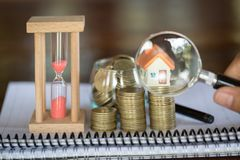 Stack coin and bar graph with grow, Hand hold a magnifying glass searching for a new home, Loan for real estate or save money for. Buy a house to family in the stock photography