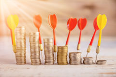 Stack of coin and red dart arrow Stock Images