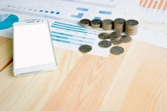 Stack coin and smartphone on table with statistic graph diagram royalty free stock photos