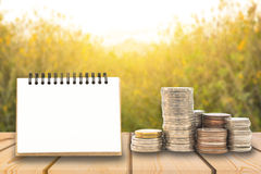 Stack of coins with blank notepad on wooden board, business and Stock Image