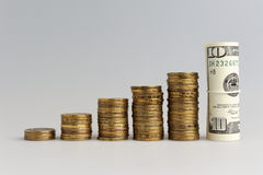 A stack of coins and bundle of dollars Stock Image