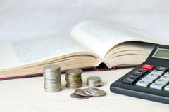 A stack of coins and a calculator in front of an open book. Concept of expensive education and low scholarship Stock Images