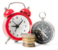 Stack of coins with compass and alarm clock Royalty Free Stock Image