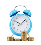 Stack of coins in front of the alarm clock Royalty Free Stock Image
