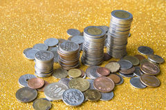 Stack of coins on golden glittering background. With coins from various countries scattering around Royalty Free Stock Images