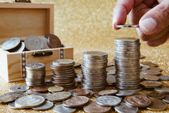 Stack of coins. Hand putting a coin on stack of coins. Golden glittering background, pile of coins in small wooden chest, with coins from various countries Stock Photo