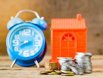 Business Finance and time of money, home loan concept. Stack of coins, home model and alarm clock on wooden background. Business Finance and time of money, home royalty free stock images