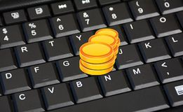 Stack of Coins on Keyboard closeup earning concept Stock Photos