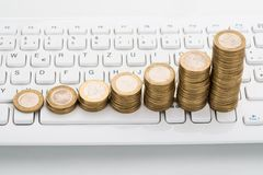 Stack of coins on keyboard Stock Photo