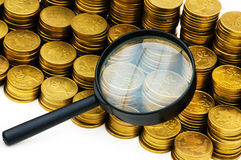 Stack of coins and magnifying glass Royalty Free Stock Photo