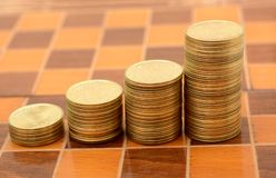 Stack of Coins making Growth graph on chess board Stock Images