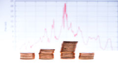 Stack of coins over financial graph Royalty Free Stock Image