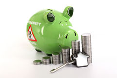 Stack of coins with piggy bank and house shape key Royalty Free Stock Images