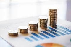 Stack of coins in a row on business chart Stock Photo