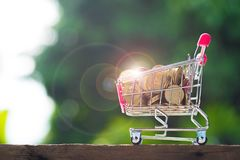 Stack of coins in shopping cart or supermarket trolley on wood t. Able in garden green nature background, business finance shopping concept idea Stock Image