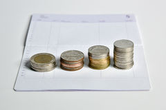 Stack of coins step up on bank saving account book Stock Photos